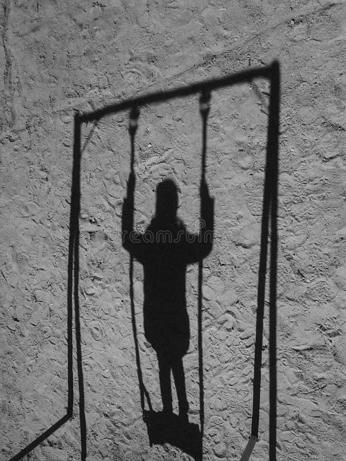 Η σκιά ενός παιδιού σε μια ταλάντευση στοκ φωτογραφίες με δικαίωμα ελεύθερης χρήσης