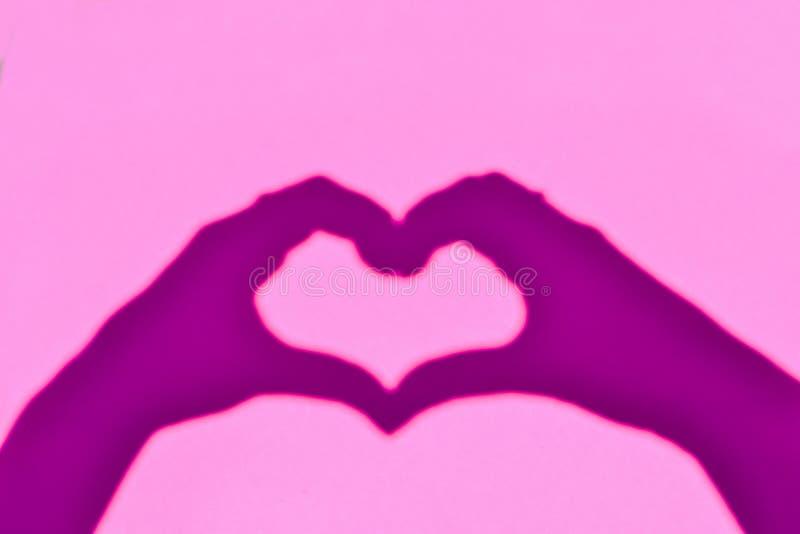 Η σκιά παραδίδει τη μορφή της καρδιάς σε ένα ρόδινο υπόβαθρο στοκ εικόνα