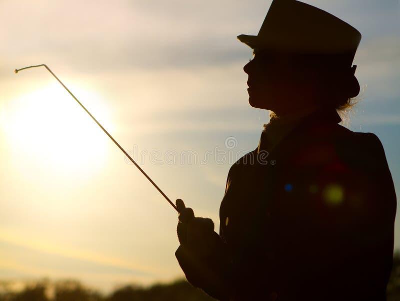 Η σκιαγραφία αναβατών της γυναίκας με κτυπά στα φω'τα ενός ήλιου στοκ εικόνα με δικαίωμα ελεύθερης χρήσης