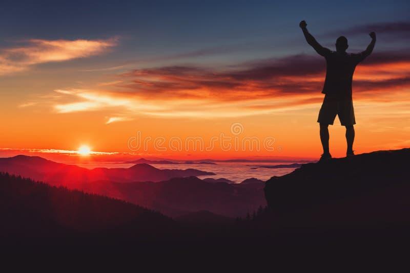 Η σκιαγραφία ατόμων στον απότομο βράχο βουνών απολαμβάνει τη panaoramic θέα Άτομο watc στοκ εικόνες με δικαίωμα ελεύθερης χρήσης