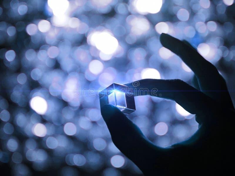 Η σκιαγραφία ενός αρσενικού χεριού που κρατά έναν κύβο γυαλιού με τον μπλε φωτισμό τεχνολογίας φώτισε επηρεασμένος και bokeh υπόβ στοκ εικόνες