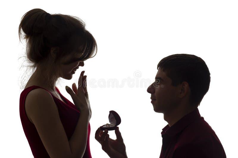 Η σκιαγραφία ενός νέου ζεύγους, ένα άτομο που στέκεται στα γόνατα και που κάνει μια πρόταση στο κορίτσι, ο τύπος δίνει το δαχτυλί στοκ εικόνες