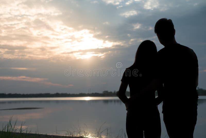 Η σκιαγραφία ενός ρομαντικού ζεύγους που στέκεται, που αγκαλιάζει το ένα το άλλο και που προσέχει το ηλιοβασίλεμα Έννοια ειδυλλίο στοκ φωτογραφία