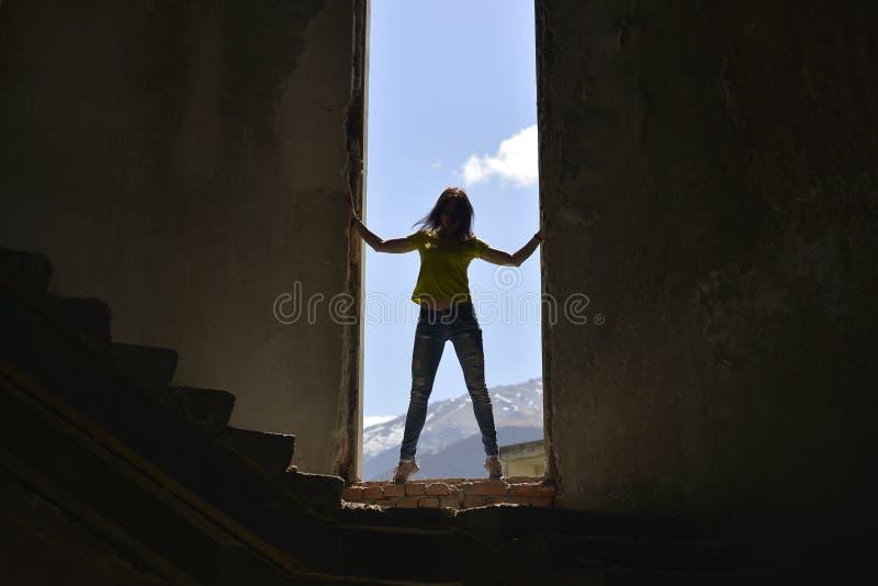 Η σκιαγραφία μιας νέας γυναίκας που στέκεται στο άνοιγμα παραθύρων κατέστρεψε ένα εγκαταλειμμένο κτήριο στοκ εικόνες