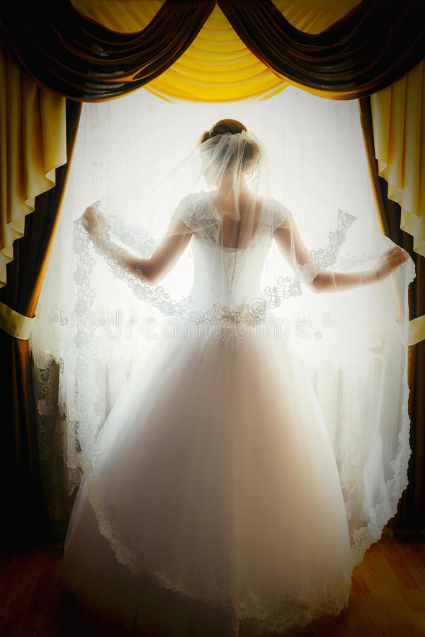 Η σκιαγραφία μιας νύφης στέκεται στο παράθυρο και κρατά ένα πέπλο Πορτρέτο μιας νύφης από την πλάτη στοκ εικόνα με δικαίωμα ελεύθερης χρήσης