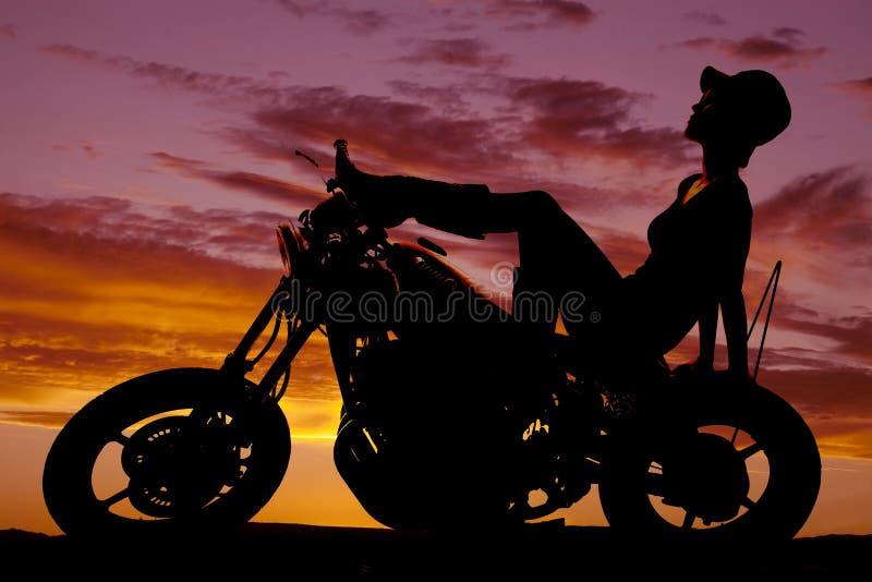 Η σκιαγραφία της γυναίκας κάθεται πίσω στο καπέλο μοτοσικλετών επάνω στοκ φωτογραφίες με δικαίωμα ελεύθερης χρήσης
