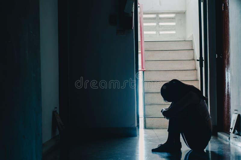 Η σκιαγραφία της συνεδρίασης κοριτσιών μόνο στις μελαχροινές, λυπημένες και σοβαρές γυναίκες που κάθονται αγκαλιάζει το γόνατο μό στοκ εικόνες με δικαίωμα ελεύθερης χρήσης
