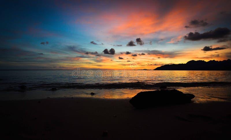 Η σκιαγραφία του ηλιοβασιλέματος παραλιών στοκ φωτογραφία