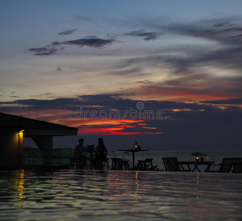 Η σκιαγραφία του ηλιοβασιλέματος προσοχής ζευγών στην παραλία στοκ φωτογραφία με δικαίωμα ελεύθερης χρήσης