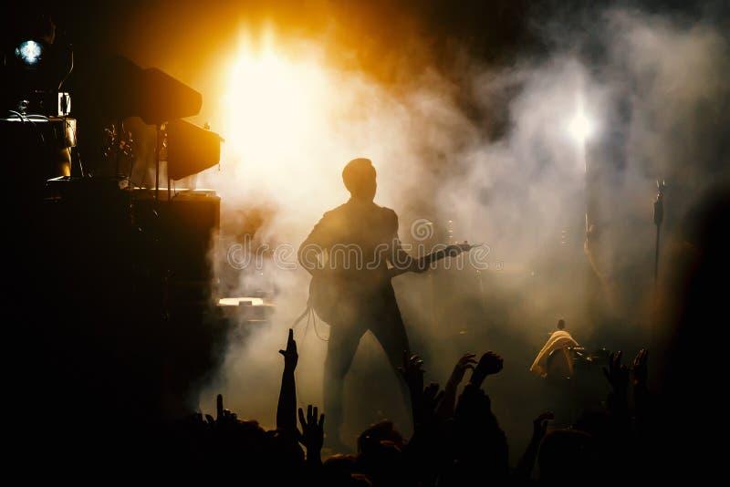Η σκιαγραφία του κιθαρίστα, κιθαρίστας αποδίδει στη σκηνή συναυλίας Σκοτεινό υπόβαθρο, καπνός, επίκεντρα συναυλίας στοκ φωτογραφία