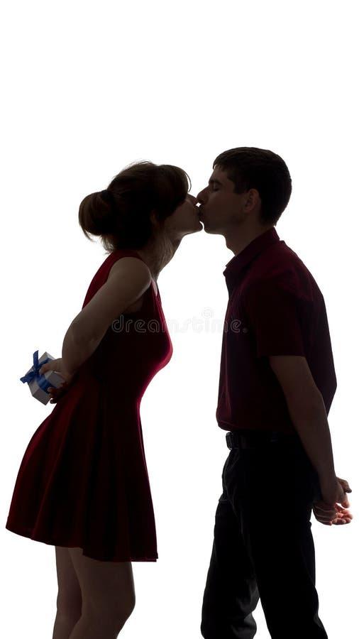 Η σκιαγραφία του κοριτσιού που φιλά έναν τύπο και που κρατά ένα κιβώτιο δώρων με ένα τόξο πίσω από την πίσω συγχαίρει, μια νεολαί στοκ φωτογραφίες με δικαίωμα ελεύθερης χρήσης