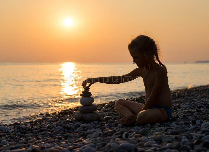 Η σκιαγραφία του κοριτσιού χτίζει την πυραμίδα από τις πέτρες στοκ εικόνα