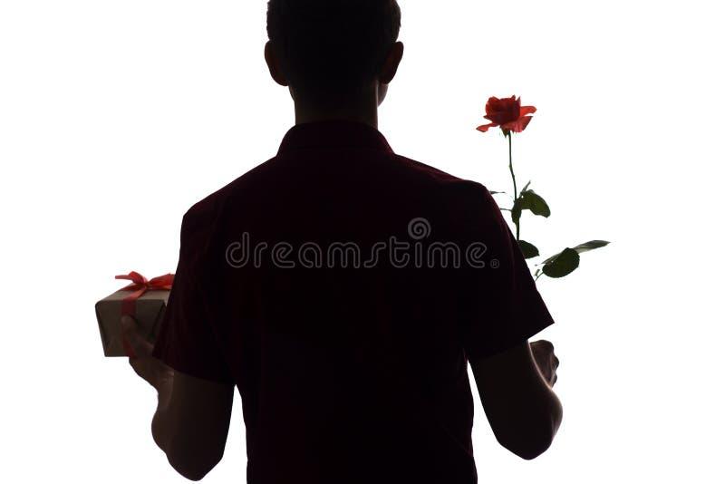 Η σκιαγραφία του νεαρού άνδρα με ένα κιβώτιο δώρων και ένα ροδαλό λουλούδι για αγαπημένο του, αγόρι συγχαίρουν απομονωμένο στο λε στοκ εικόνες