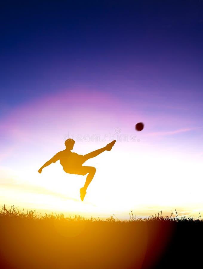 Η σκιαγραφία του ποδοσφαιριστή κλωτσά τη σφαίρα στοκ φωτογραφία