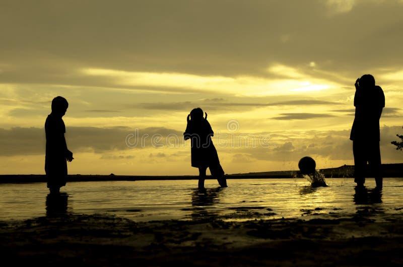 Η σκιαγραφία τρία αγόρια παίζει τη σφαίρα και τη στιγμή παραλιών η σφαίρα που πέφτει κατά τη διάρκεια της ανατολής ηλιοβασιλέματο στοκ φωτογραφίες με δικαίωμα ελεύθερης χρήσης