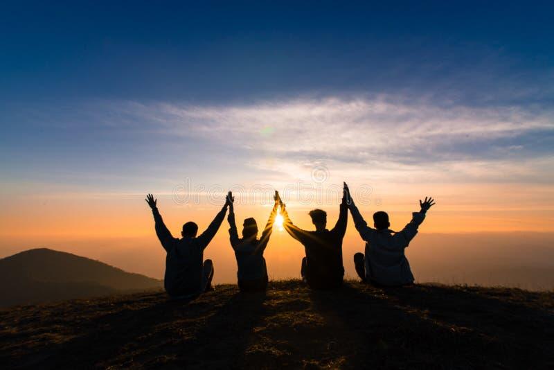Η σκιαγραφία των φίλων τινάζει τα χέρια επάνω και τη συνεδρίαση μαζί στον ήλιο στοκ εικόνες