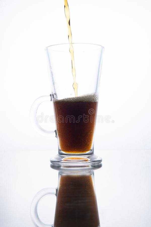 Η σκοτεινή μπύρα χύνεται σε μια κούπα σε ένα άσπρο υπόβαθρο στοκ εικόνες με δικαίωμα ελεύθερης χρήσης