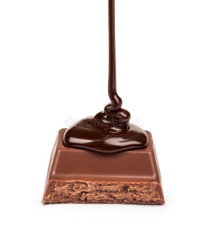 Η σκοτεινή σοκολάτα χύνεται επάνω σε ένα κομμάτι στοκ εικόνα με δικαίωμα ελεύθερης χρήσης