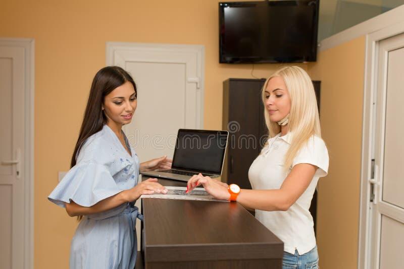 Η σκοτεινός-μαλλιαρή γυναίκα εργάζεται στην υποδοχή Εργάζεται σε ένα σαλόνι ομορφιάς Μιλά με τον πελάτη και παρουσιάζει κάτι στοκ φωτογραφία