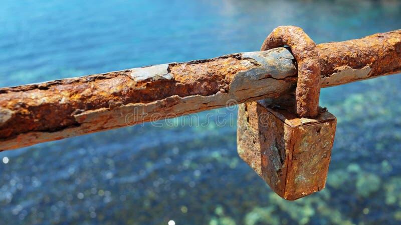 Η σκουριασμένο κλειδαριά ή το λουκέτο αγάπης σε ένα τμήμα της σύνδεσης αλυσίδων περιφράζει στοκ εικόνα