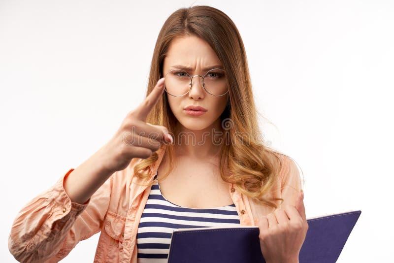 Η σοβαρή γυναίκα με τη βαρύθυμη έκφραση, δείχνει με το αντίχειρα άμεσα στη κάμερα, έχει το βλέμμα, που ντύνεται στο ριγωτό πουκάμ στοκ φωτογραφίες