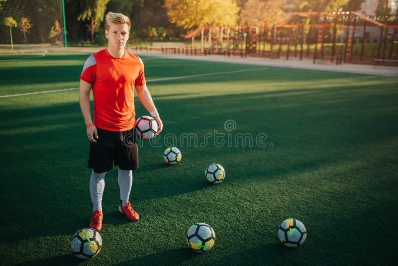 Η σοβαρή και συγκεντρωμένη νέα στάση ποδοσφαιριστών στο χορτοτάπητα και κοιτάζει στη κάμερα Κρατά μια σφαίρα διαθέσιμη Άλλος είνα στοκ φωτογραφία με δικαίωμα ελεύθερης χρήσης