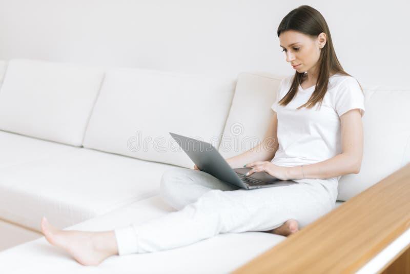 Η σοβαρή νέα γυναίκα σκέφτεται στις ιδέες για την ανάπτυξη της συνεδρίασης ιστοχώρου στον καναπέ στοκ εικόνα