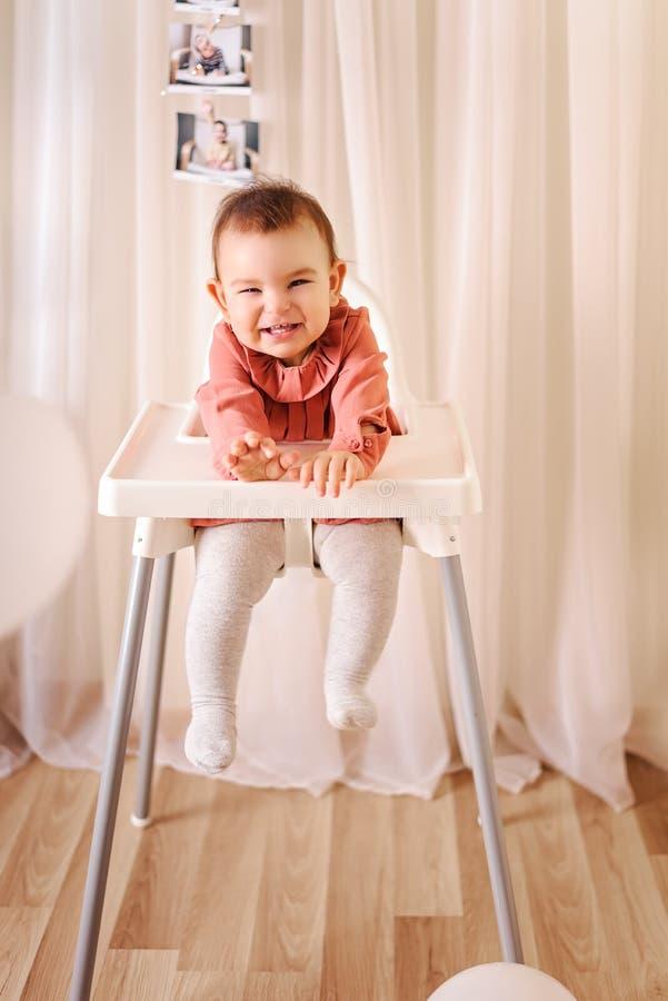 Η σοβαρή συνεδρίαση μωρών στο highchair στο σπίτι στο εσωτερικό στοκ φωτογραφίες