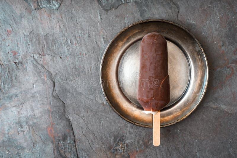 Η σοκολάτα κάλυψε popsicle στο μεταλλικό πιάτο στη τοπ άποψη υποβάθρου πετρών στοκ εικόνα με δικαίωμα ελεύθερης χρήσης