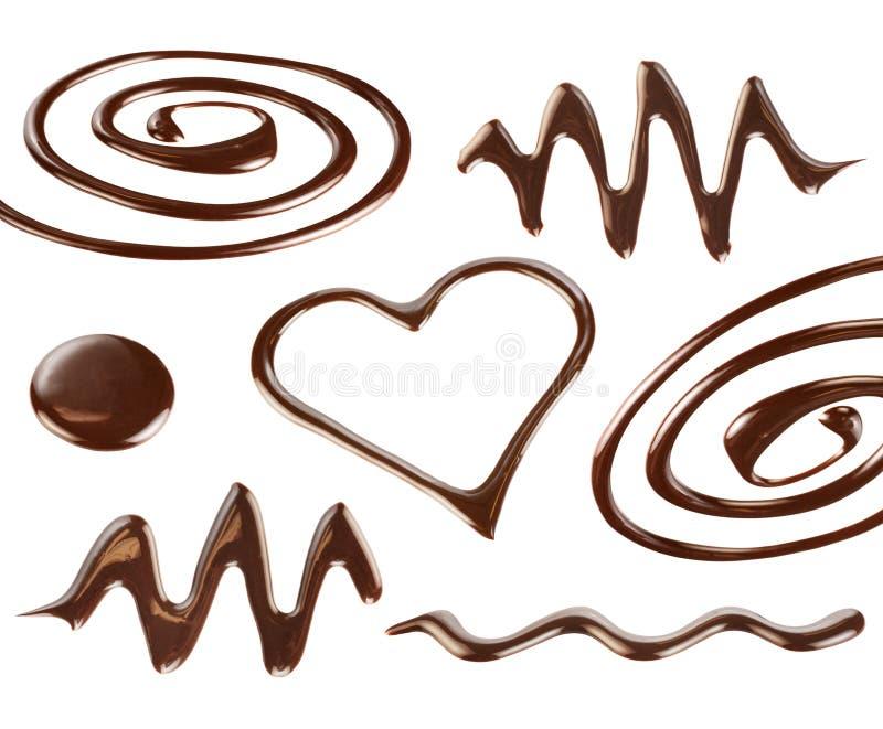 Η σοκολάτα υγρού γάλακτος ρίχνει και καταβρέχει τα διακοσμητικά στοιχεία στοκ εικόνες