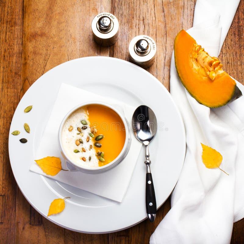 Η σούπα κολοκύθας με τους σπόρους κρέμας και κολοκύθας σε ένα λευκό καλύπτει στο wo στοκ φωτογραφίες με δικαίωμα ελεύθερης χρήσης
