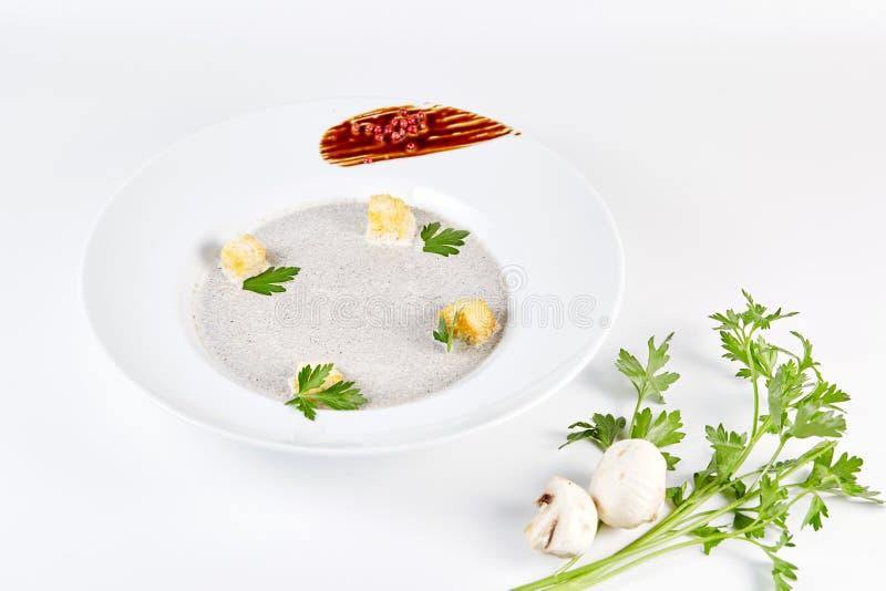 Η σούπα κρέμας μανιταριών με croutons, τα χορτάρια και τα καρυκεύματα πέρα από το άσπρο υπόβαθρο κλείνουν επάνω - σπιτική vegan χ στοκ εικόνα με δικαίωμα ελεύθερης χρήσης