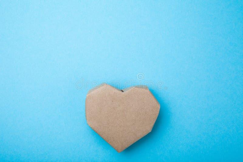 Η σπιτική καρδιά έκανε από το ανακυκλωμένο έγγραφο για ένα μπλε υπόβαθρο, κενό διάστημα για το κείμενο στοκ φωτογραφία με δικαίωμα ελεύθερης χρήσης