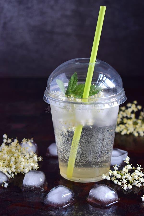 Η σπιτική λεμονάδα elderflower με τα λουλούδια λεμονιών και elderberry στο πλαστικό φλυτζάνι με τη σφαίρα καλύπτει την κάψουλα κα στοκ φωτογραφίες με δικαίωμα ελεύθερης χρήσης