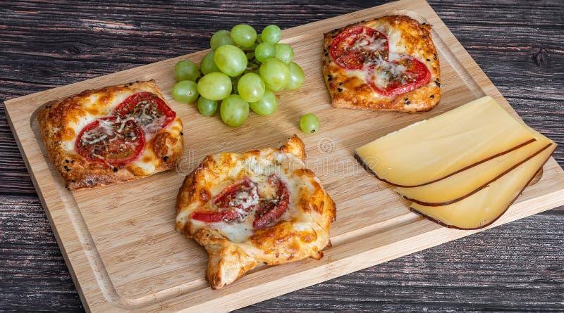 Η σπιτική πίτα με τις ντομάτες και το τυρί βρίσκονται σε έναν ξύλινο πίνακα δίπλα στα σταφύλια και τα κομμάτια του τυριού στοκ εικόνες