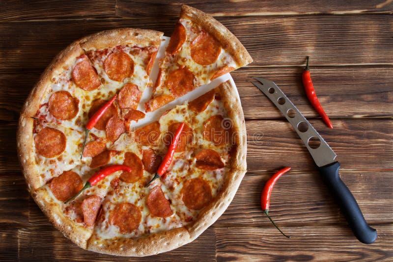 Η σπιτική πίτσα με pepperoni και τα κόκκινα πιπέρια τσίλι βρίσκεται δίπλα σε ένα μαχαίρι τυριών σε μια φυσική ξύλινη επιφάνεια πο στοκ εικόνα