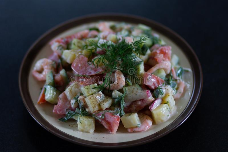 Η σπιτική σαλάτα με τις γαρίδες και τα φρέσκα λαχανικά με το γιαούρτι που διακοσμήθηκε με το μάραθο στο πιάτο στο μαύρο πίνακα στοκ εικόνες