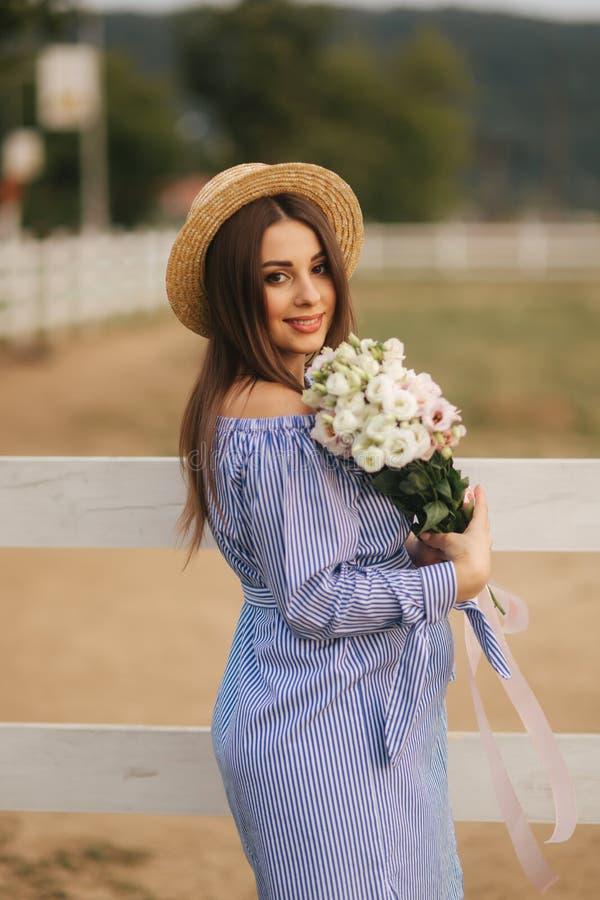 Η στάση γυναικών Georgeus μπροστά από το αγρόκτημα και κρατά μια ανθοδέσμη του λουλουδιού στα χέρια Ανθοδέσμη Beautuful Γυναίκα σ στοκ φωτογραφία