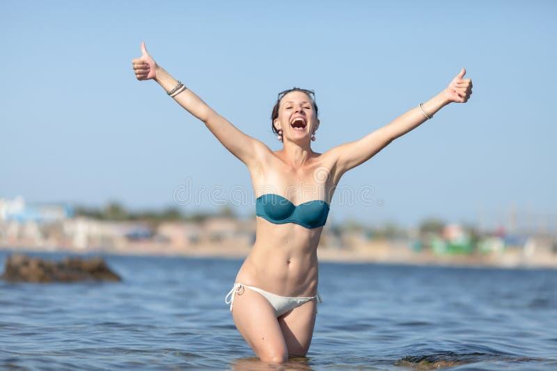 Η στάση κοριτσιών στο θαλάσσιο νερό, παρουσιάζει αντίχειρες και φωνάζει στοκ φωτογραφίες