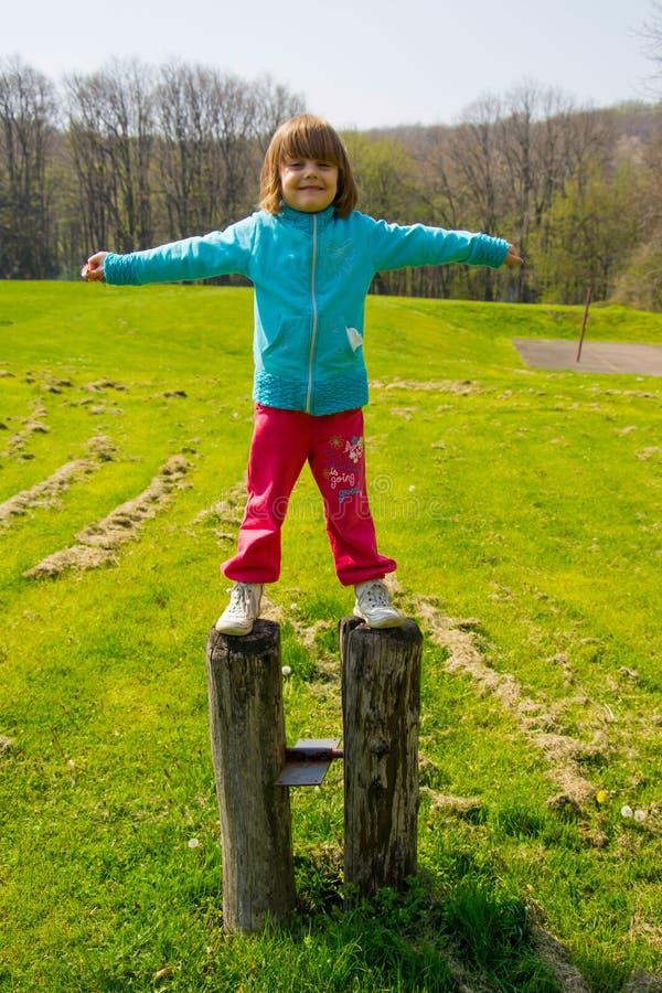 Η στάση μικρών κοριτσιών στα δύο μεγάλα συνδέεται το πάρκο στοκ φωτογραφία με δικαίωμα ελεύθερης χρήσης
