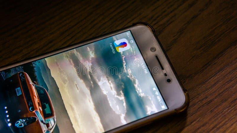Η στενή επάνω άποψη της εφαρμογής FaceApp σε ένα αρρενωπό smartphone στοκ φωτογραφίες