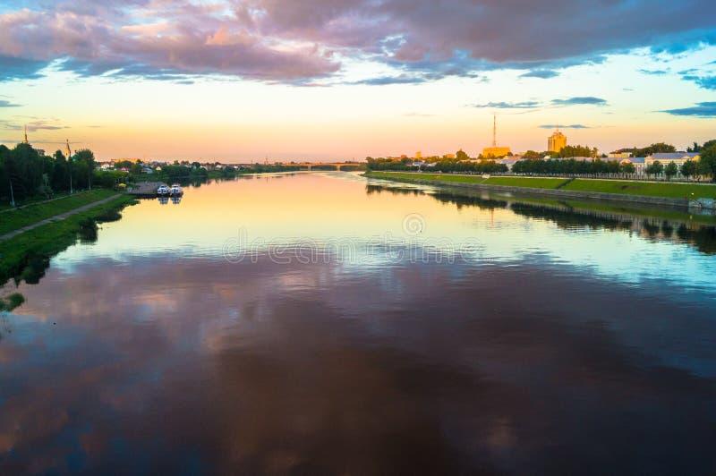 Η στιλπνή επιφάνεια καθρεφτών του ποταμού του Βόλγα απεικονίζει το δραματικό ουρανό ηλιοβασιλέματος Πόλη Tver, Ρωσία στοκ εικόνες