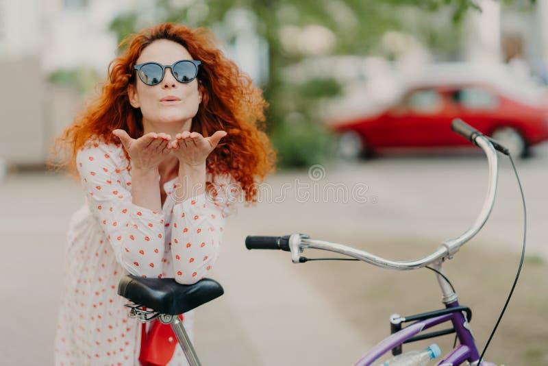 Η στοργική redhead γυναίκα στέλνει το φιλί αέρα στον εραστή στην οδό, κρατά τους φοίνικες κοντά στο στόμα, φορά γύρω από τις σκιέ στοκ φωτογραφία