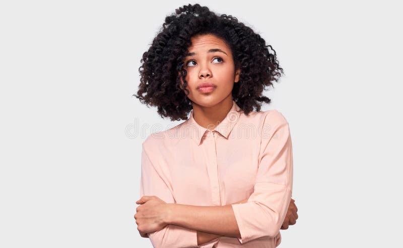 Η στοχαστική γυναίκα αφροαμερικάνων έχει την έκφραση σκέψης, ανατρέχοντας μακριά στο κενό διάστημα αντιγράφων στοκ φωτογραφία