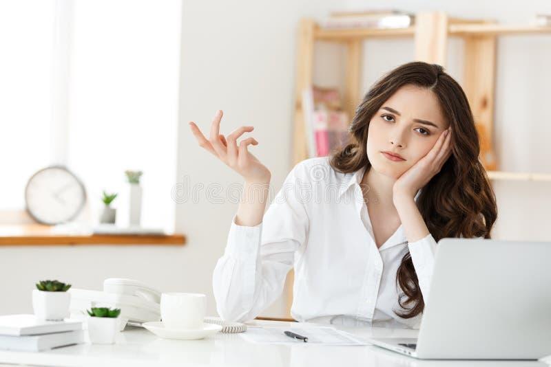 Η στοχαστική γυναίκα με το χέρι κάτω από το πηγούνι που τρυπήθηκε στην εργασία, που φαίνεται μακριά καθμένος κοντά στο lap-top, α στοκ εικόνα