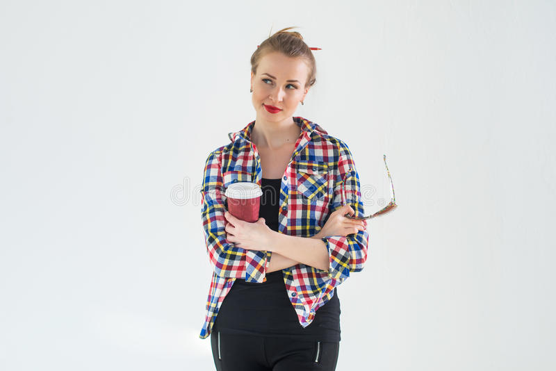 Η στοχαστική νέα γυναίκα που φορά το ελεγμένο πουκάμισο που στέκεται με τα χέρια της δίπλωσε πέρα από το στήθος, κρατώντας τον κα στοκ φωτογραφίες