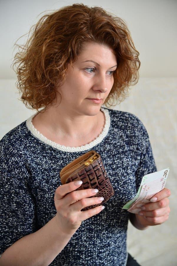Η στοχαστική ρωσική γυναίκα τραβά από τα ρούβλια πορτοφολιών της στοκ φωτογραφίες