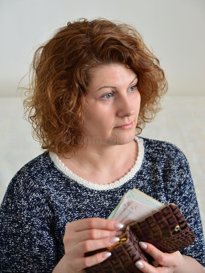 Η στοχαστική ρωσική γυναίκα τραβά από τα ρούβλια πορτοφολιών της στοκ εικόνα με δικαίωμα ελεύθερης χρήσης