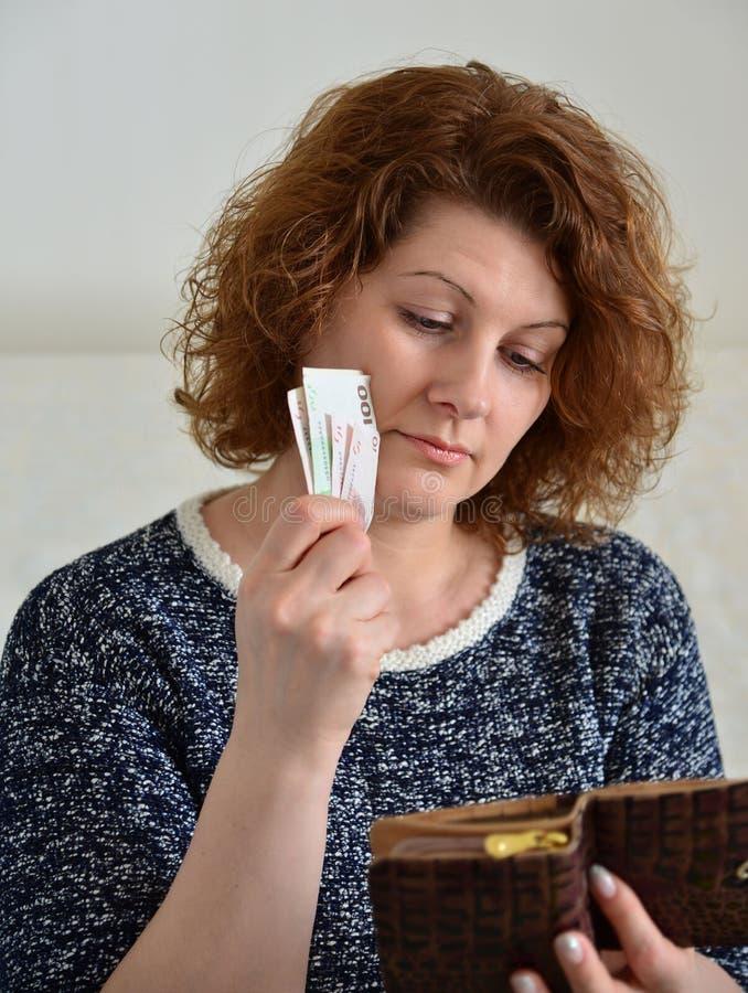Η στοχαστική ρωσική γυναίκα τραβά από τα ρούβλια πορτοφολιών της στοκ εικόνες