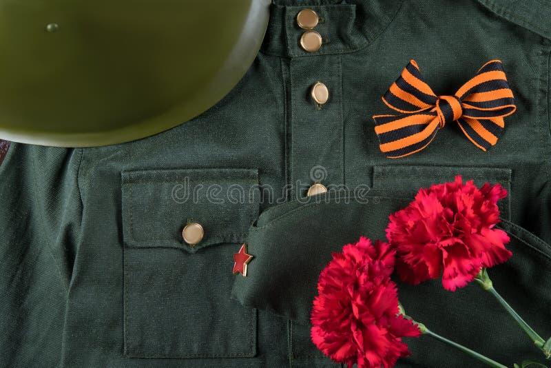 Η στρατιωτική στολή, το κράνος, η πορτοκαλιά κορδέλλα και τα κόκκινα λουλούδια, σχεδίασαν υπέροχα την εικόνα για την 9η Μαΐου στοκ φωτογραφίες με δικαίωμα ελεύθερης χρήσης
